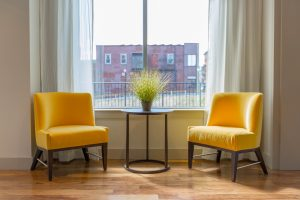 Simplistic home design of two yellow chairs facing a small table with plant