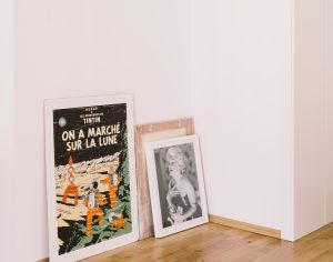 Several paintings and posters leaning against the wall to be used in an interior design project