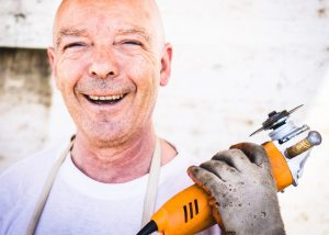 Close up of woodworm specialist holding tool and smiling